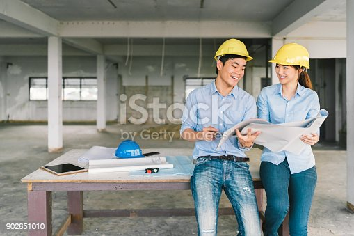 681142982 istock photo Young Asian engineers couple working together on building blueprint at construction site or factory. Civil engineering, industrial business partner, or home renovation service concept. With copy space 902651010
