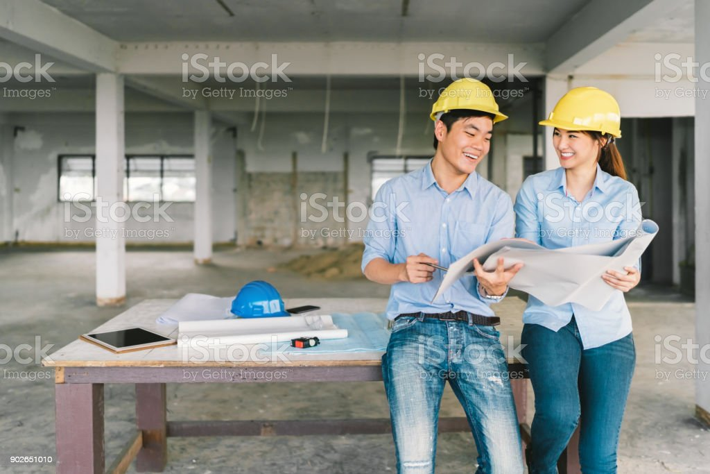 Young Asian engineers couple working together on building blueprint at construction site or factory. Civil engineering, industrial business partner, or home renovation service concept. With copy space stock photo