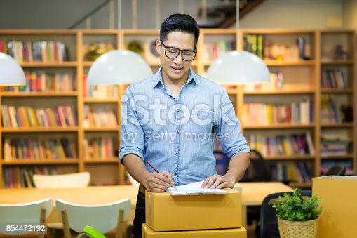 istock Young Asian entrepreneur packing product into the box for his customers after received order at home office. Conceptual for startup small businesses starting own company and online marketing. 854472192