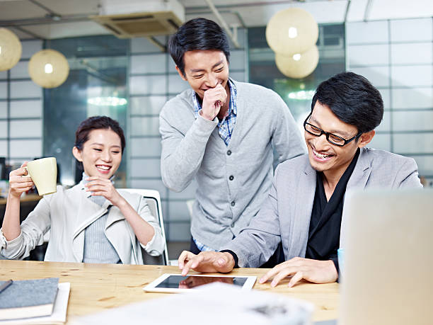 young asian entrepreneurs working in office - 談笑する ストックフォトと画像