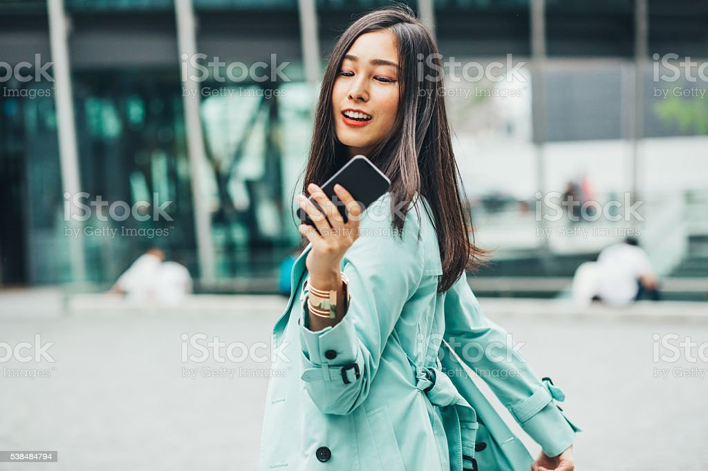 Beautiful Japanese woman holding a mobile phone looking back, walking...