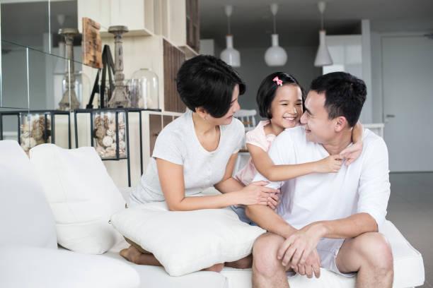 Jovem família asiática em casa. - foto de acervo