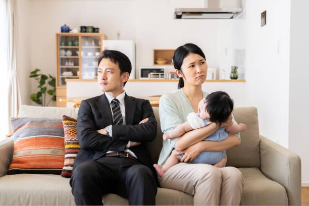 リビング ルームで若いアジア家族 - 両親 ストックフォトと画像