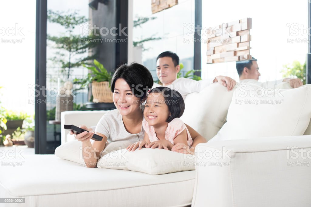 Young Asian family watching TV at home. stock photo