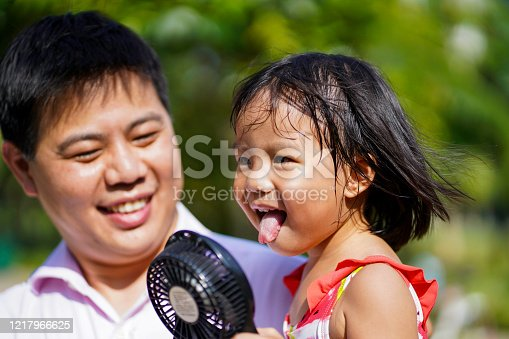 Young Asian Father helping daughter fan herself with portable fan in hot weather.