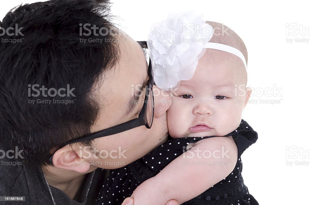 Young Asian father kissing daughter on cheek. royalty-free stock photo