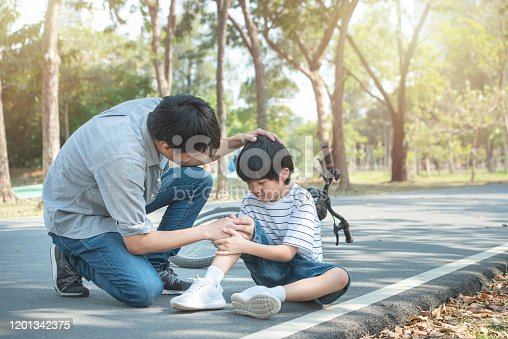 istock Young asian father of dad calms son that fell from the bike and he get injury on knee and leg while have weekend leisure in public park,accident can happen everywhere and every time. 1201342375