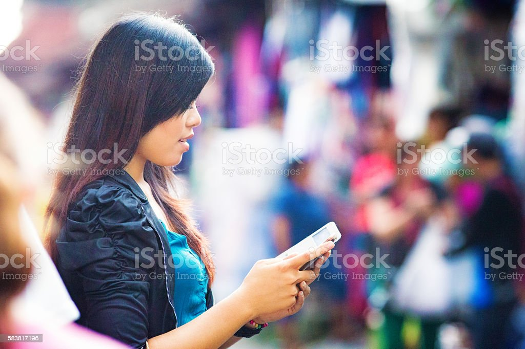 Young Asian female absorbed by her mobile AR video game stock photo