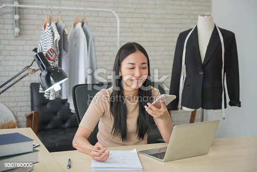 836871418 istock photo young asian female designer looking to the phone while sitting at desktop with sketches of new clothes in her fashion-studio 930760000