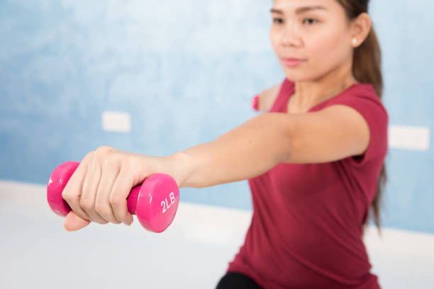 young asian female doing exercises with dumbbells - hand grip stock photos and pictures