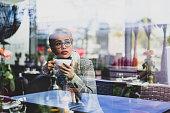 Blondie woman drinking hot drink in cafeteria.