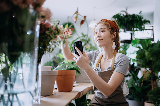 Young Asian female florist, owner of small business flower shop, taking pictures of flowers and plants. Updating and posting on her online shop and selling products online. Running an online business, e-commerce, online shopping with technology