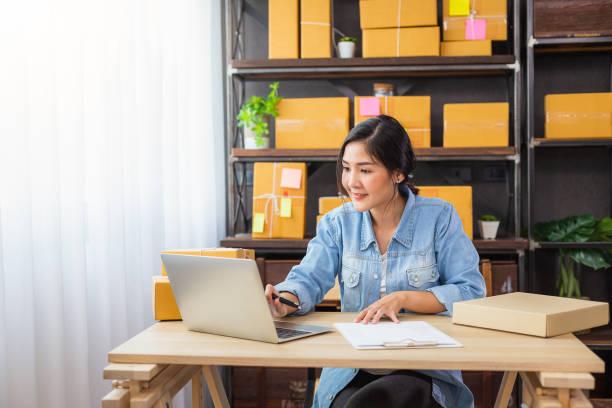 freelancer wanita muda asia menggunakan laptopnya dan bekerja di rumah, pemilik wanita bisnis kecil atau memulai pengusaha bisnis kecil yang bekerja secara online pemasaran kemasan pengiriman kotak kemasan - bisnis online potret stok, foto, & gambar bebas royalti