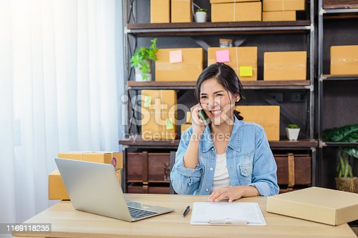 836871418 istock photo Young Asian female freelancer using mobile phone and working at home, Small business female owner or Start up small business entrepreneur working online marketing packaging box delivery 1169118235