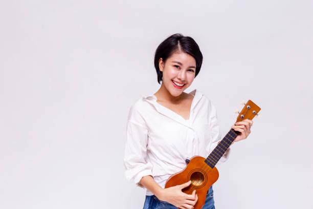 junge weibliche asiatin spielt ukulele strand gitarre in weißen hintergrund isoliert. - ukulele songs stock-fotos und bilder