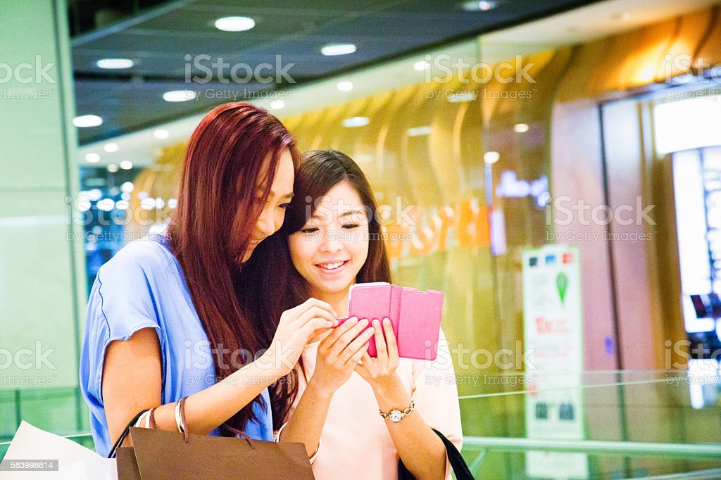 Young Asian female showing friend how to play mobile game stock photo