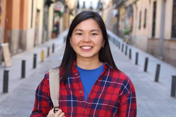 Fêmea asiática nova que sorri ao ar livre - foto de acervo