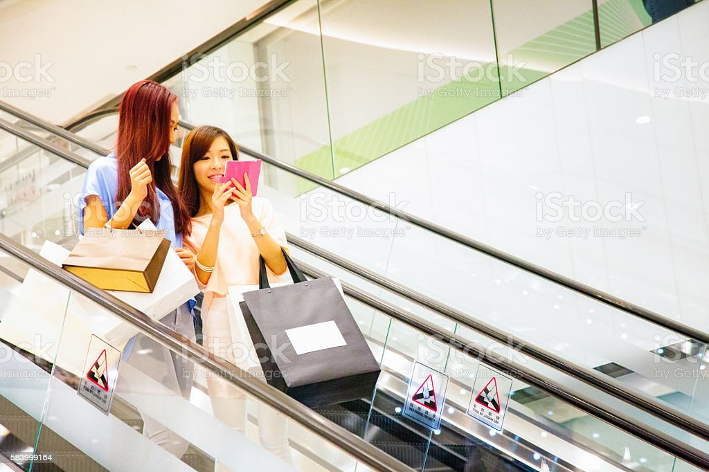 Young Asian female teaching mobile game with friend on escalator stock photo