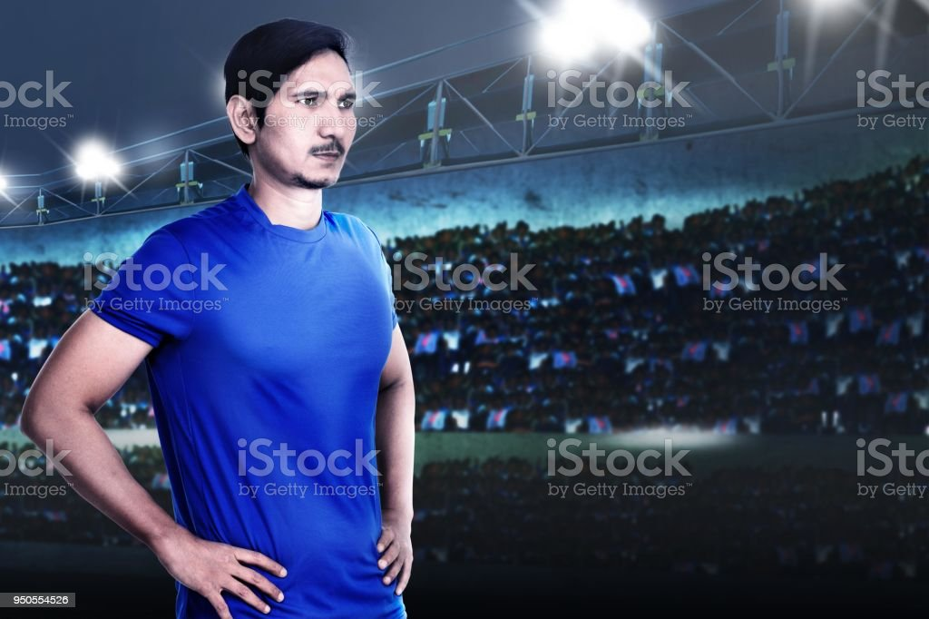 Young asian footballer with determination for win on the stadium
