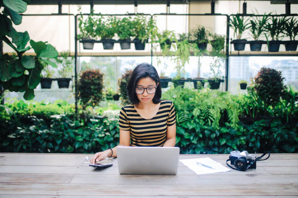 Young Asian freelancer woman finishing up with work stock photo