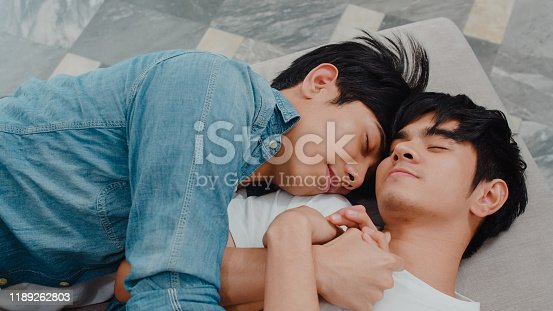 504371332 istock photo Young Asian gay couple sleep together at home. Teen korean LGBTQ+ men happy relax rest lying on bed in bedroom at house in the morning. 1189262803