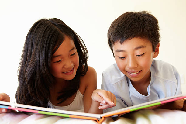 Young Asian girl and boy reading book stock photo