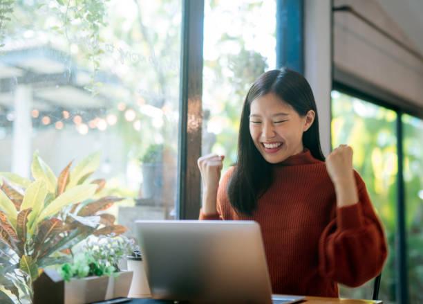 jovem menina asiática comemorar sucesso ou pose feliz com portátil - excitação - fotografias e filmes do acervo