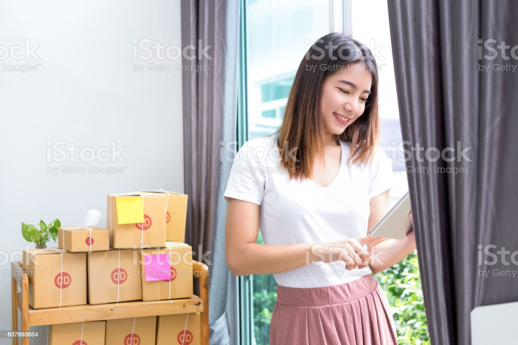 Young asian girl freelancer business private working at home office with holding tablet, laptop, note, packaging delivery online market on purchase or checking orders to customer. stock photo