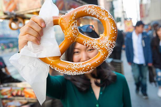 young asian girl holding pretzel in nyc - 椒鹽蝴蝶圈 個照片及圖片檔