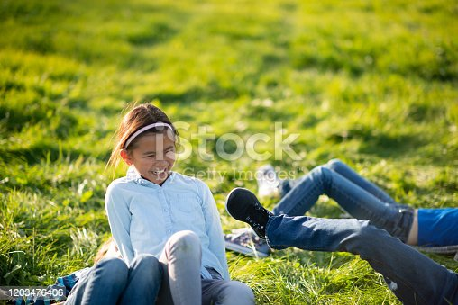A young Asian girl lays in the grass with her multi-ethnic peers, on a warm, sunny, fall day.  She is laughing and giggling as they roll around and have fun together in the fresh air.  Each youth is dressed casually in denim pants and fall attire.