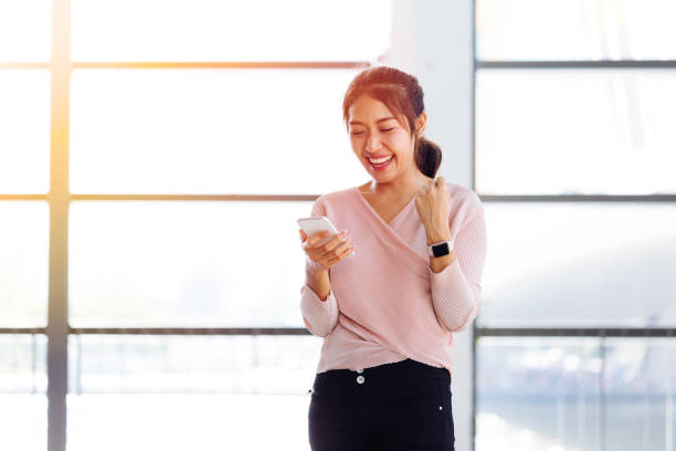 Young Asian girl looking at her mobile phone and get excited inside the building stock photo