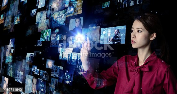 istock Young asian girl looking hologram screens. Streaming video. Social media. 1169711640