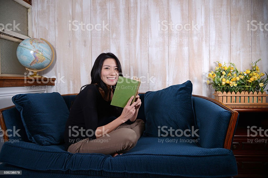 Young Asian girl reading on a couch stock photo