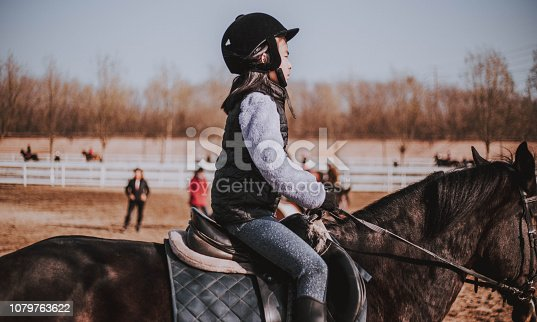 Young Asian girl riding her horse