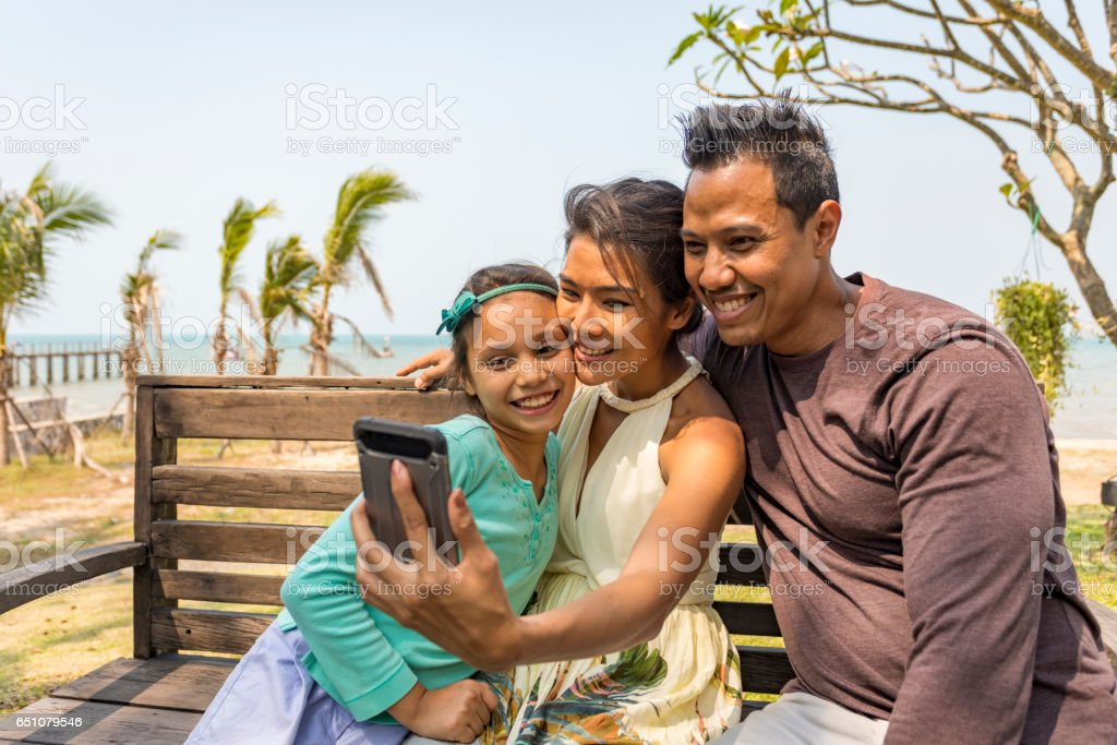 Young Asian Girl Taking a Selfie on Vacation With Her Parents stock photo
