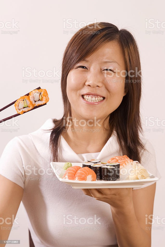 Young Asian Girl With 2 Sushi Maki Between Chopsticks royalty-free stock photo
