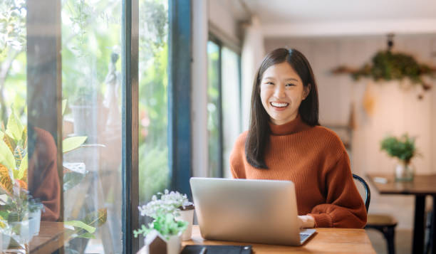 young Asian girl working at a coffee shop with a laptop Happy young Asian girl working at a coffee shop with a laptop korean ethnicity stock pictures, royalty-free photos & images