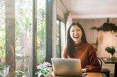 ノート パソコンでコーヒー ショップで働く若いアジアの女の子