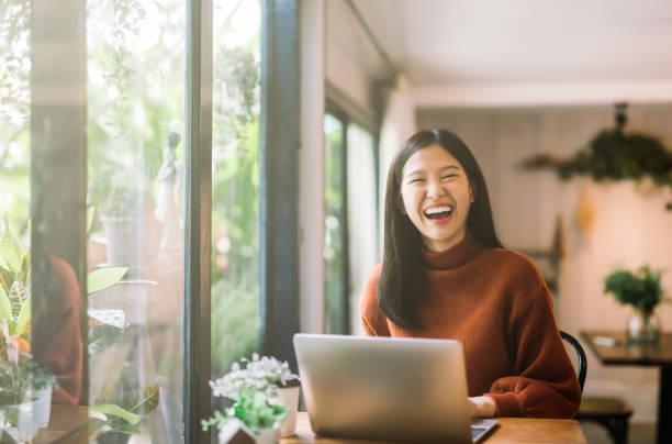 年輕的亞洲女孩在咖啡店工作與筆記本電腦 - 少女 個照片及圖片檔