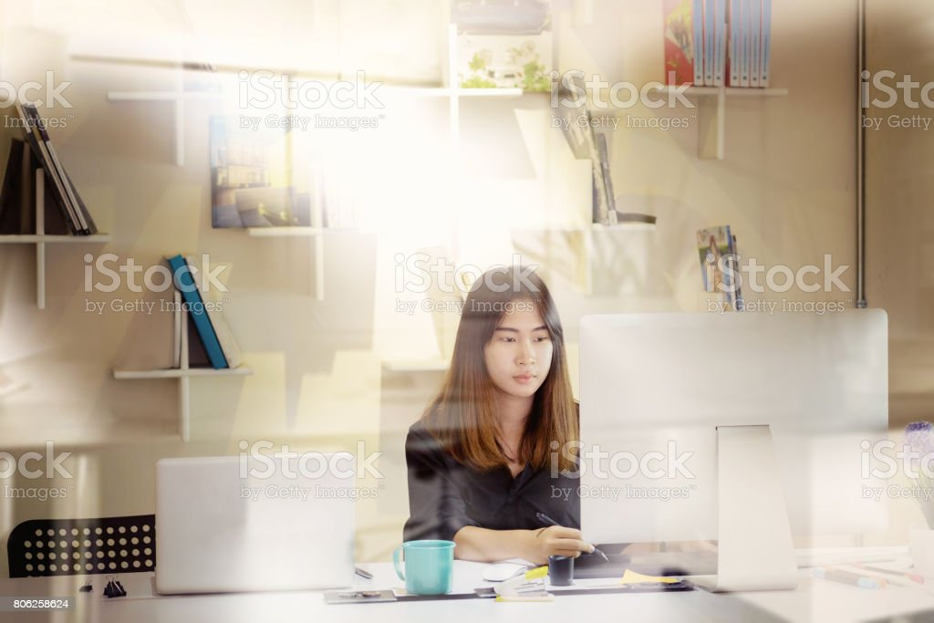 Young asian graphic designer working on computer stock photo