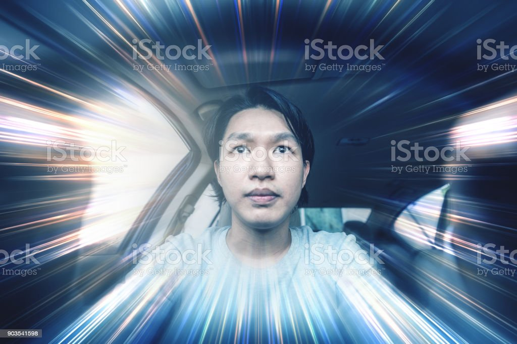 Young Asian guy driving modern car, selective focus. Driving fast with motion stock photo