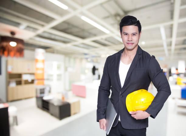 Junge asiatische hübsche Architektin mit Computer in den Händen auf Lagerhintergrund. – Foto