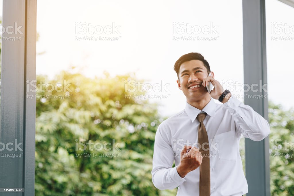 Young asian handsome businessman talking on phone and happiness for work. royalty-free stock photo