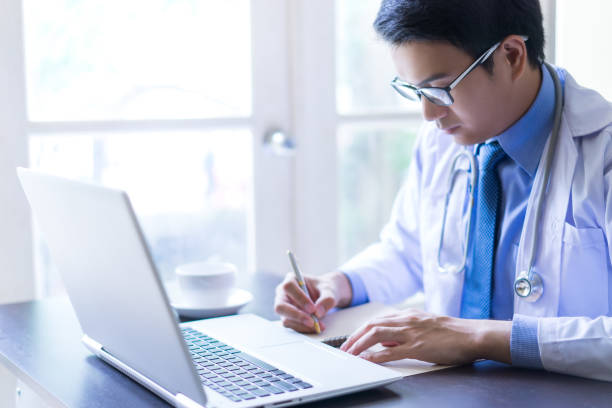 Young asian handsome doctor writing on notebook while using his laptop computer with serious face