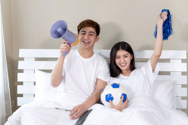 Young Asian handsome husband and beautiful wife feel great when the soccer they cheering is winner champ in the bed room stock photo