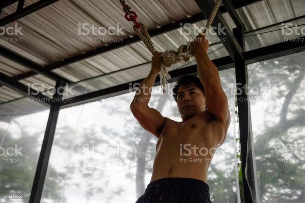Young Asian Handsome muscled man, 20-30 years old, exercise and practice with trx rope while working out in gym sport club, Happy exercise with good healthy lifestyle stock photo