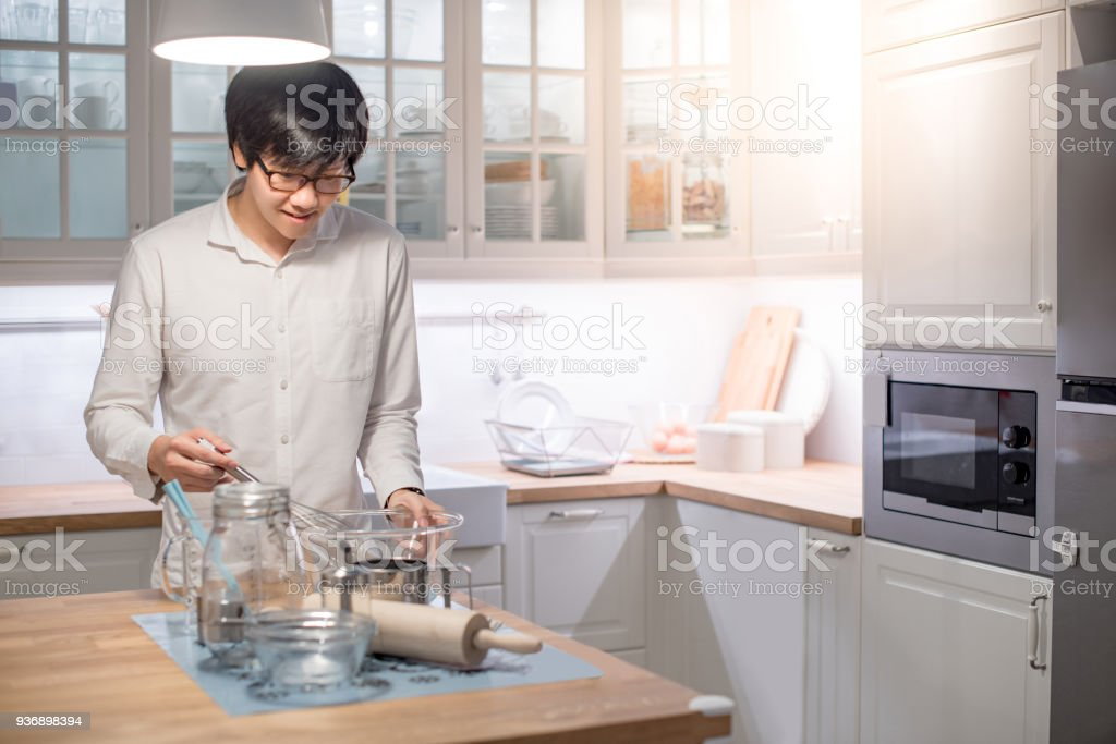 Young Asian happy man standing in front of counter in kitchen preparing cooking wares for meal stock photo