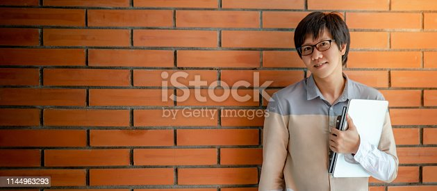 947303582 istock photo Young Asian happy man university student with glasses holding laptop computer and books standing by orange brick wall. Campus lifestyle in education building. Research and scholarship concepts 1144963293