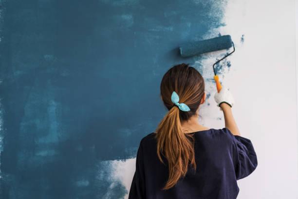 молодая азиатская счастливая женщина картина интерьер валь - краска стоковые фото и изображения