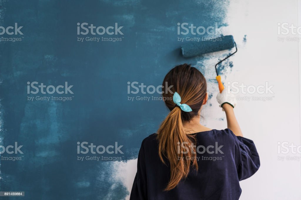 Young asian happy woman painting interior wal stock photo